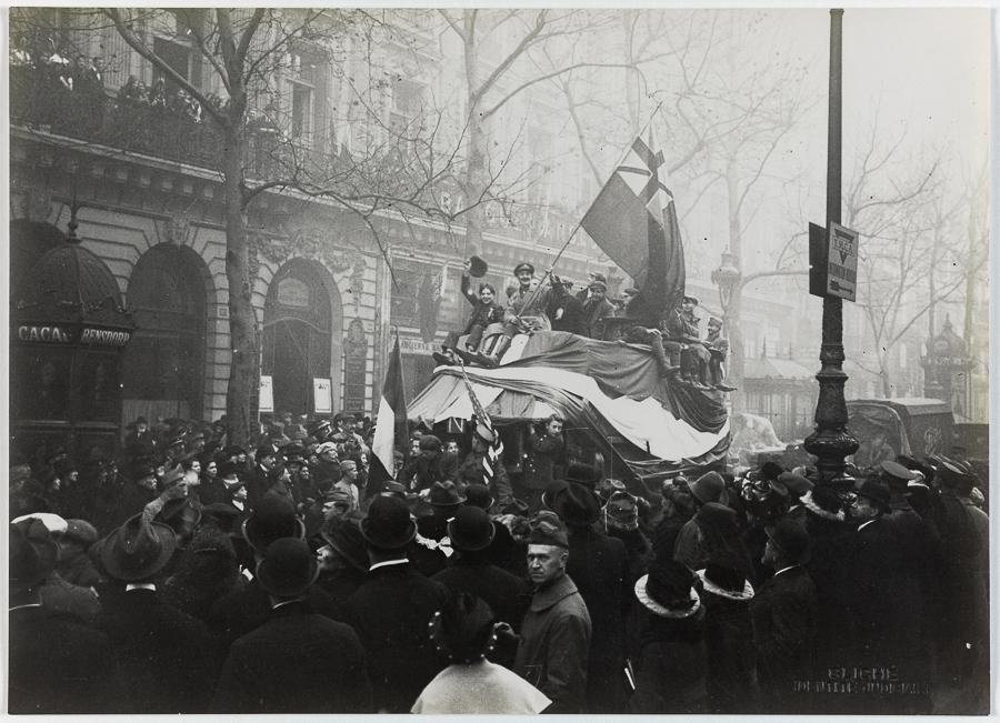 Guerre 1914-1918. Le jour de l'Armistice. La foule sur les camions anglais vers le n° 19, boulevard des Capucines. Paris (IXème arr.), 11 novembre 1918.