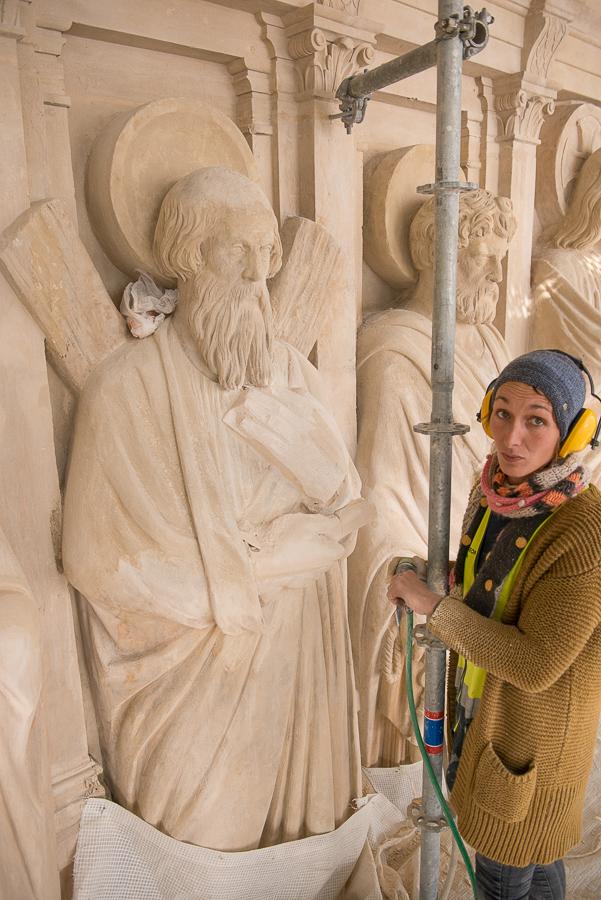 Emilie, sculptrice sur pierre devant la statue de Saint André