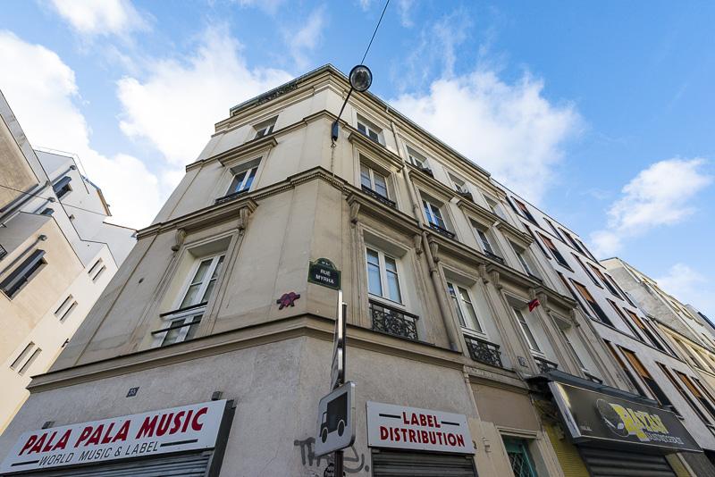 Vue sur un ancien immeuble de style Louis Philippe à l'angle de la rue Myrha et de la rue Léon occupé par le label de music Pala Pala Goutte d'or