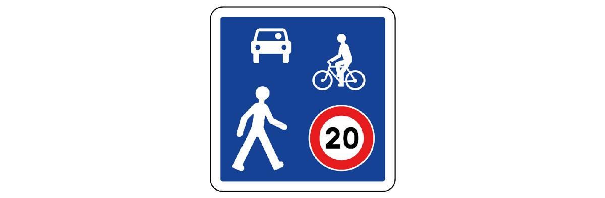Entrée de zone de rencontre. Dans cette zone limitée à 20 km/h, le cycliste est prioritaire  sur les voitures, mais il  doit laisser la priorité  aux piétons.