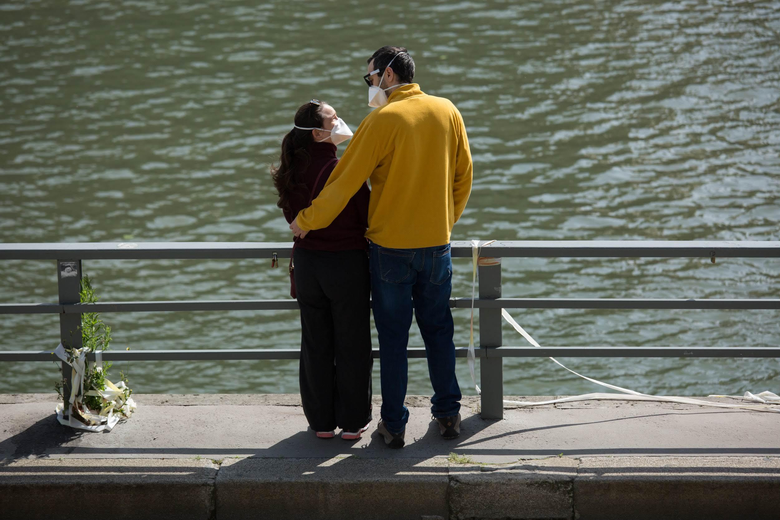 Couple portant un masque sur les Rives de Seine au soleil
