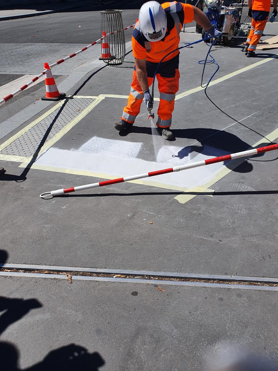 Un agent applique de la peinture infrarouge sur le revêtement de la chaussée.