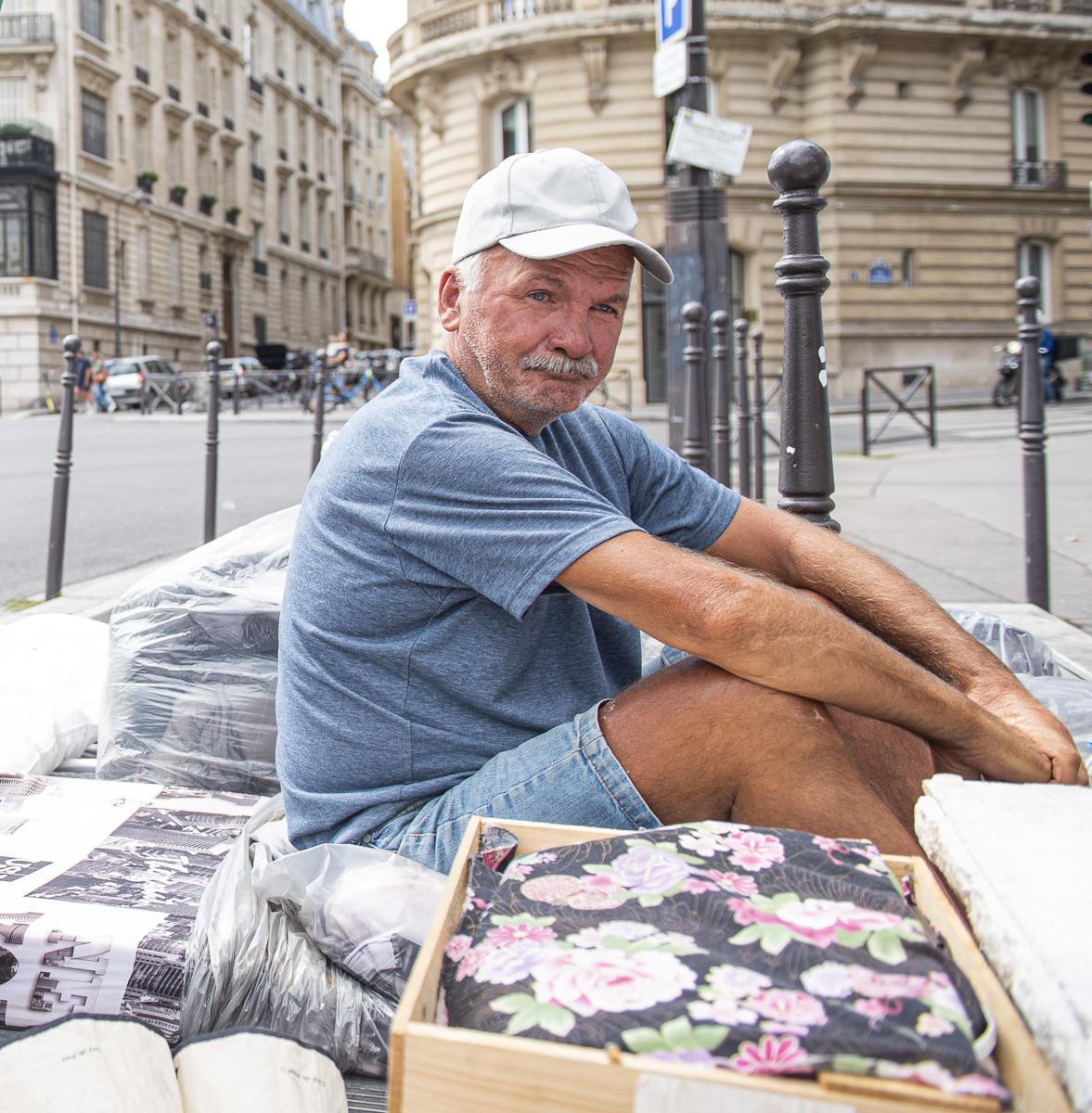 Personne sans abris assis sur un trottoir