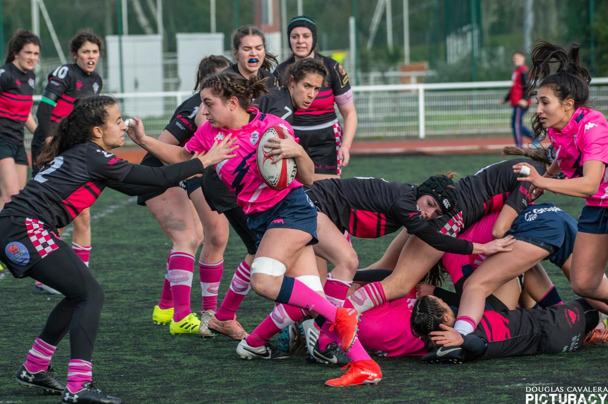 De jeunes femmes jouent au rugby.