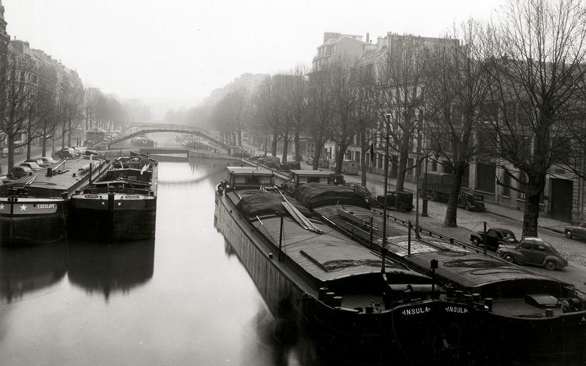 Péniches stationnant à couple sur le canal Saint-Martin à Paris dans les années 50 avec la passerelle Alibert en arrière-plan