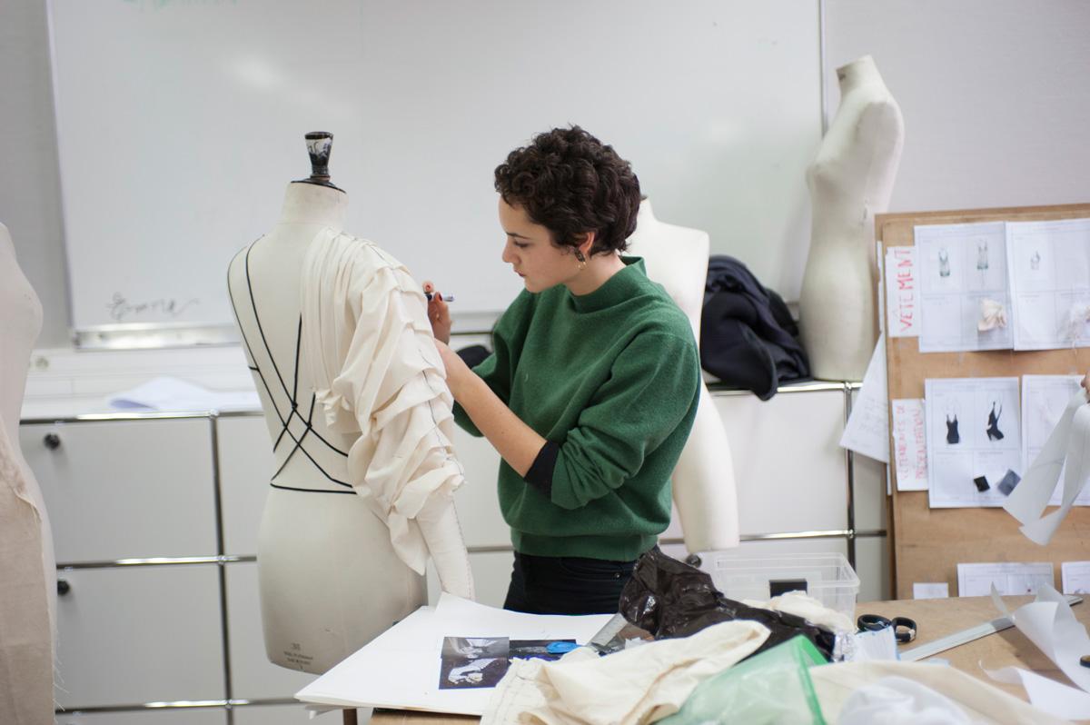 Une élève confectionne un vêtement sur mannequin.