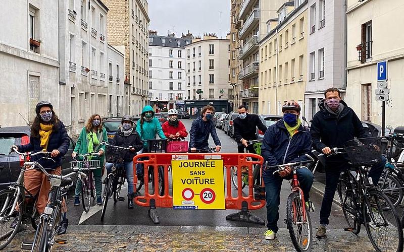 """Photo du groupe de la déambulation dans le 12e autour d'une barrière à laquelle est accroché un panneau """"Journée sans voiture"""""""