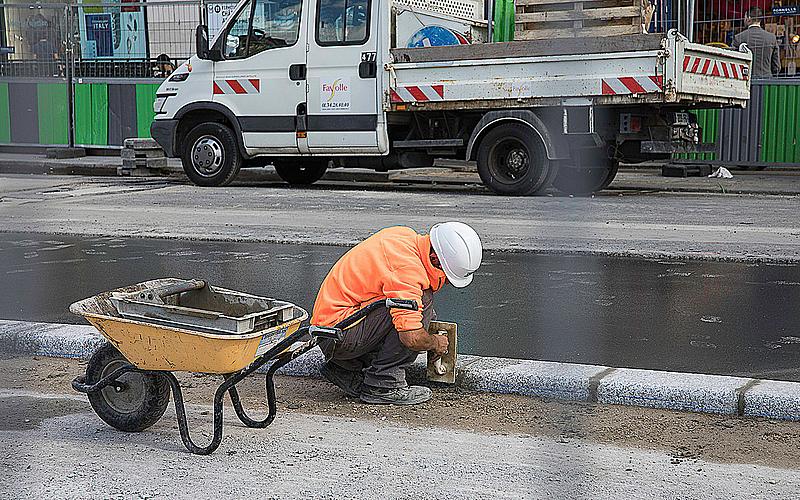 un ouvrier refait un trottoir