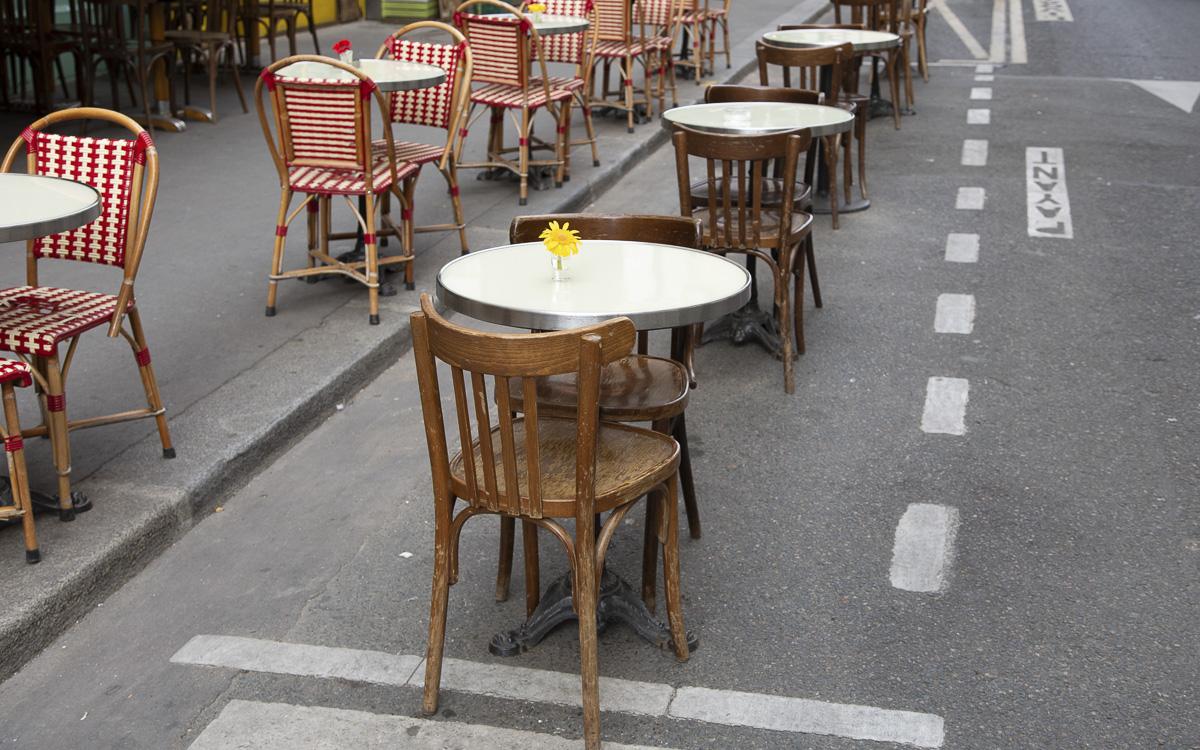 Place de parking dans la rue, sur laquelle est posée une dizaine de tables de café et leurs chaises