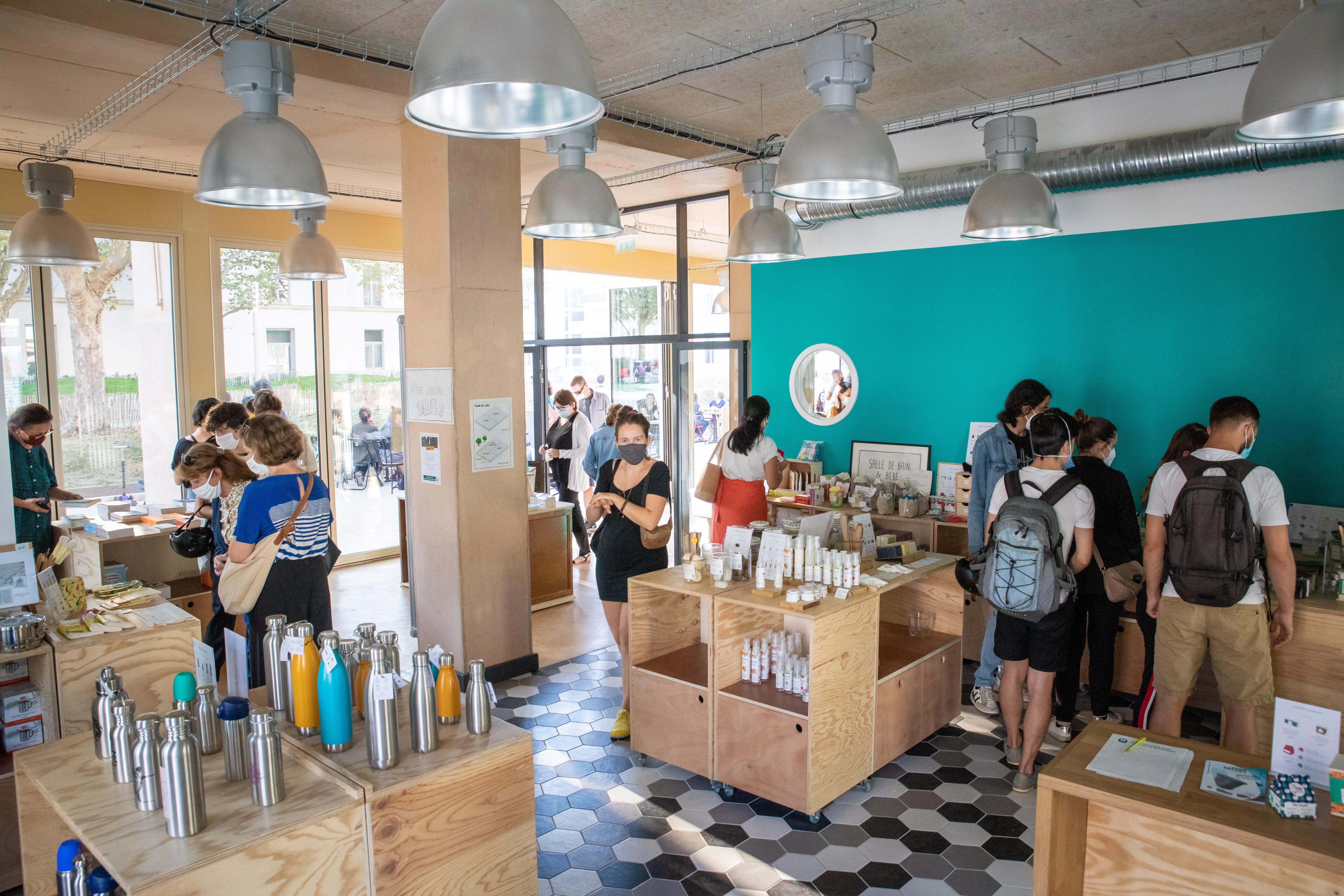 Intérieur de la boutique de la Maison du Zéro Déchet, présentant tous les produits durables, avec quelques visiteurs et visiteuses