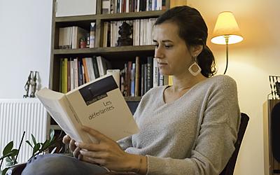 Une Parisienne lit un livre chez elle.