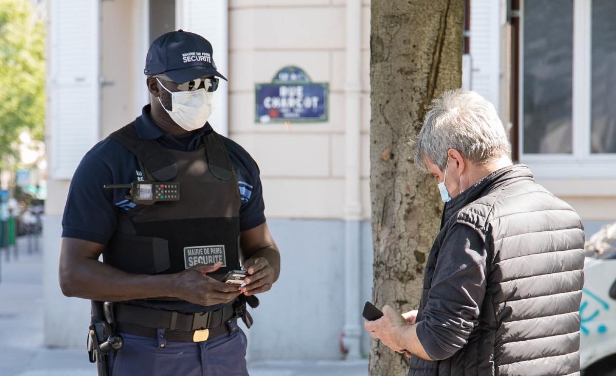 Un inspecteur de sécurité de la Ville de Paris contrôle l'attestation d'un passant.