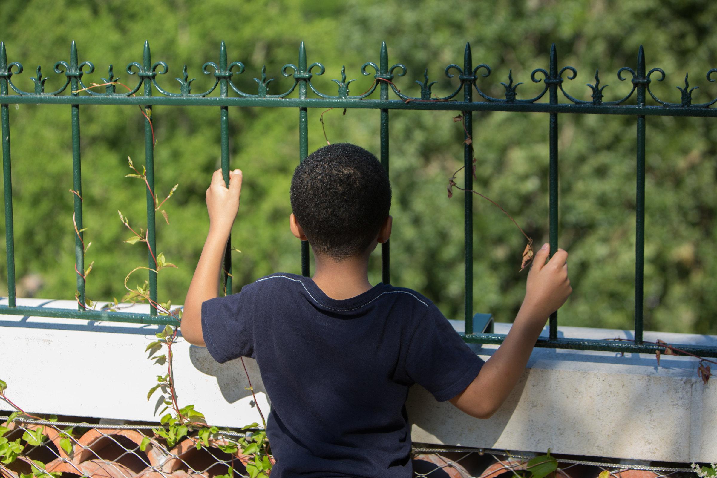 Un enfant se tient de dos devant une grille de jardin.