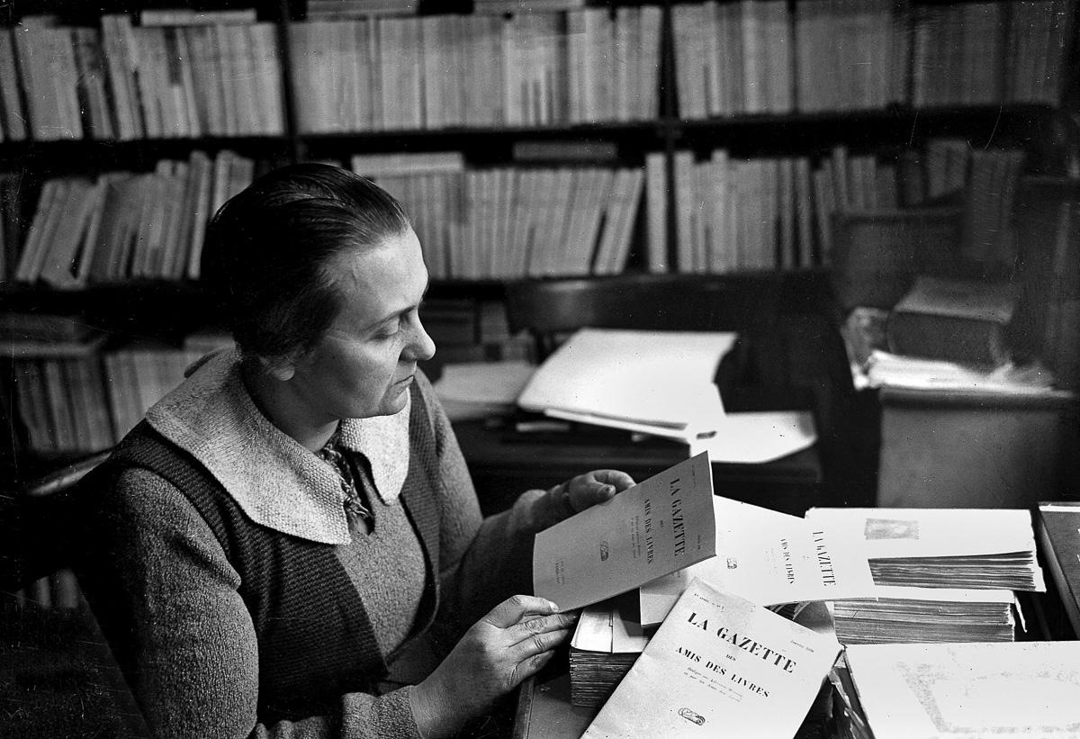 """Adrienne Monnier dans sa librairie """"La Maison des Amis des Livres"""", rendez-vous du monde littéraire de l'entre-deux-guerres, rue de l'Odéon, à Paris. Présentation du numéro un de sa  Gazette."""