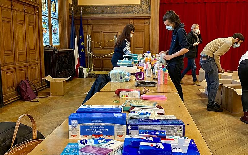 De nombreux produits d'hygiène collectés sur une longue table, avec des bénévoles d'affairant à les trier