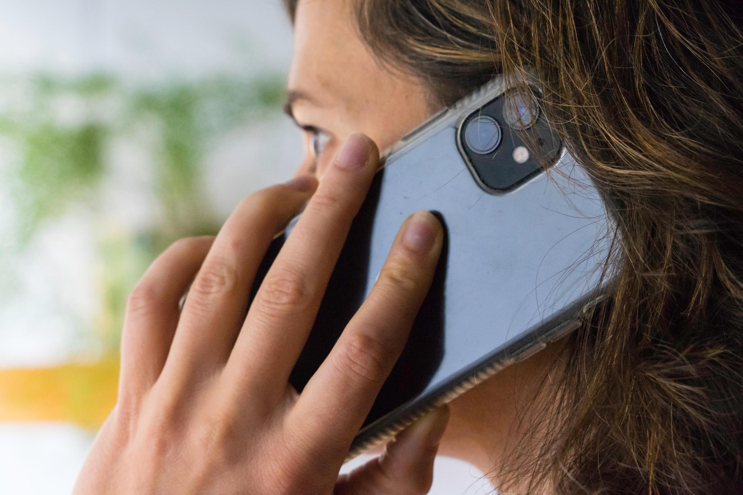 Une personne tient un téléphone à la main posé sur son oreille.