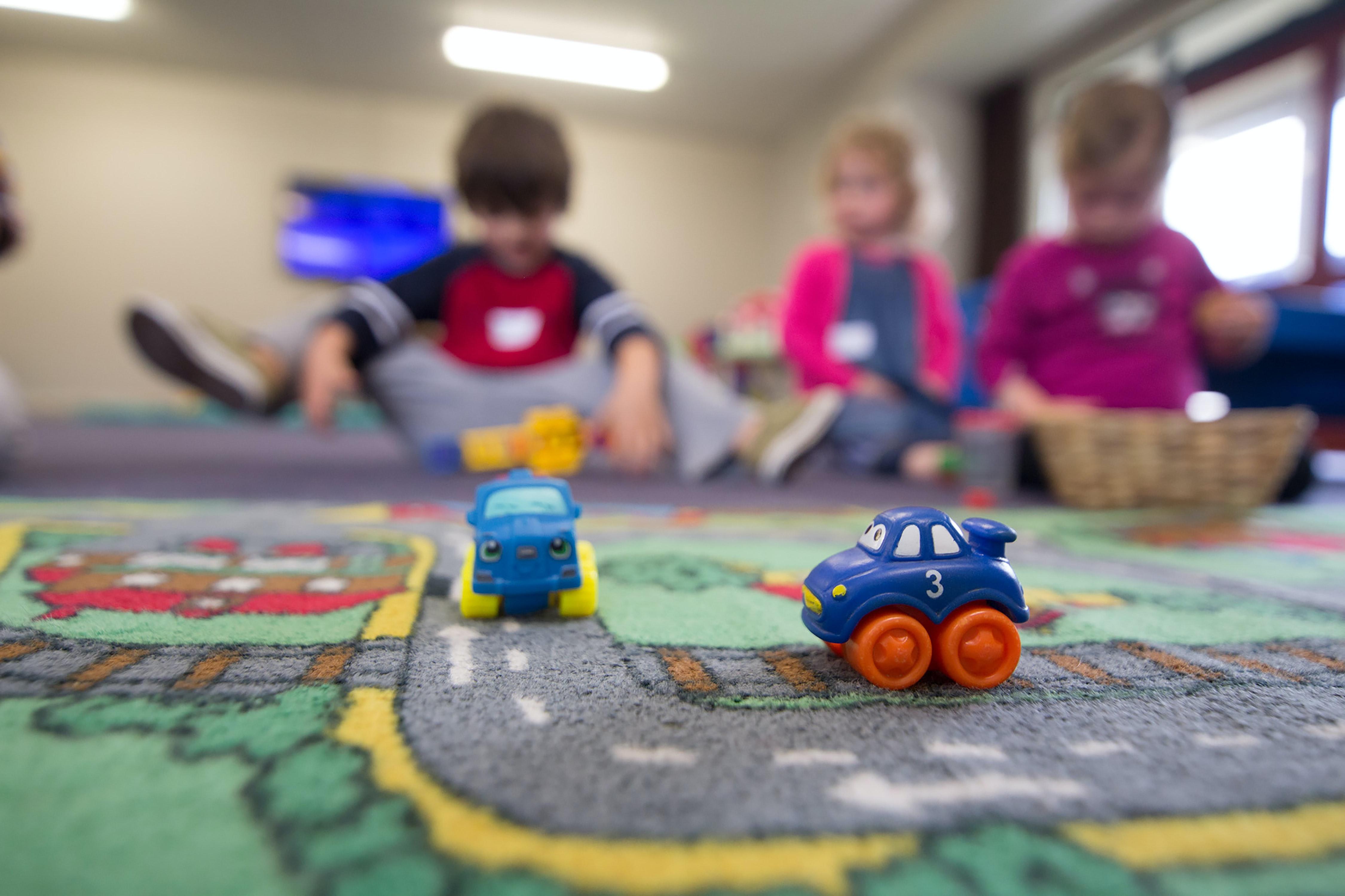 Deux petites voitures (jouets) en premier plan, 3 enfants flous au fond, dans une crèche