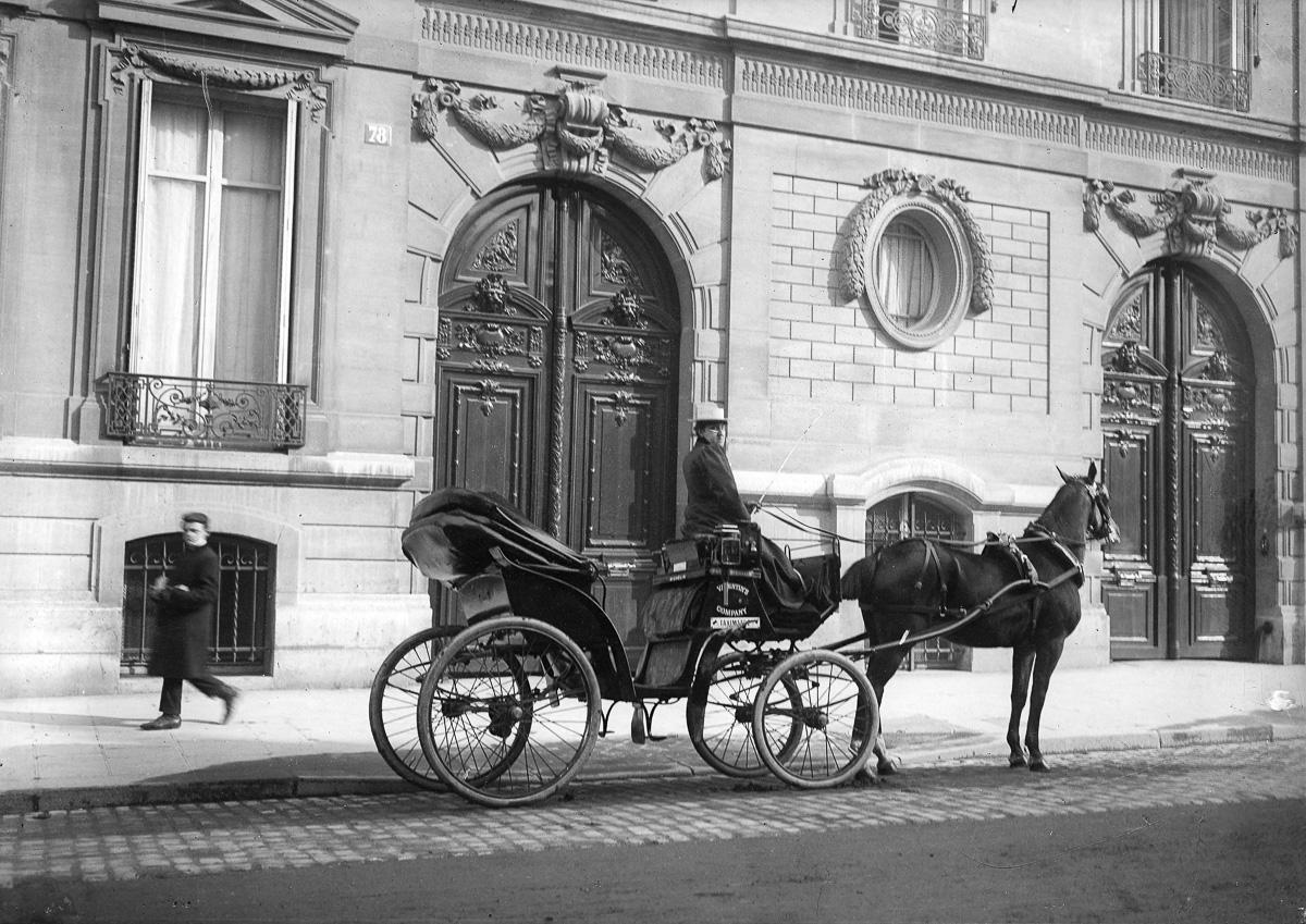 Femme cocher et son taxi hippomobile devant deux portes cochères de la fin du XVIIIème siècle. Paris, vers 1900.