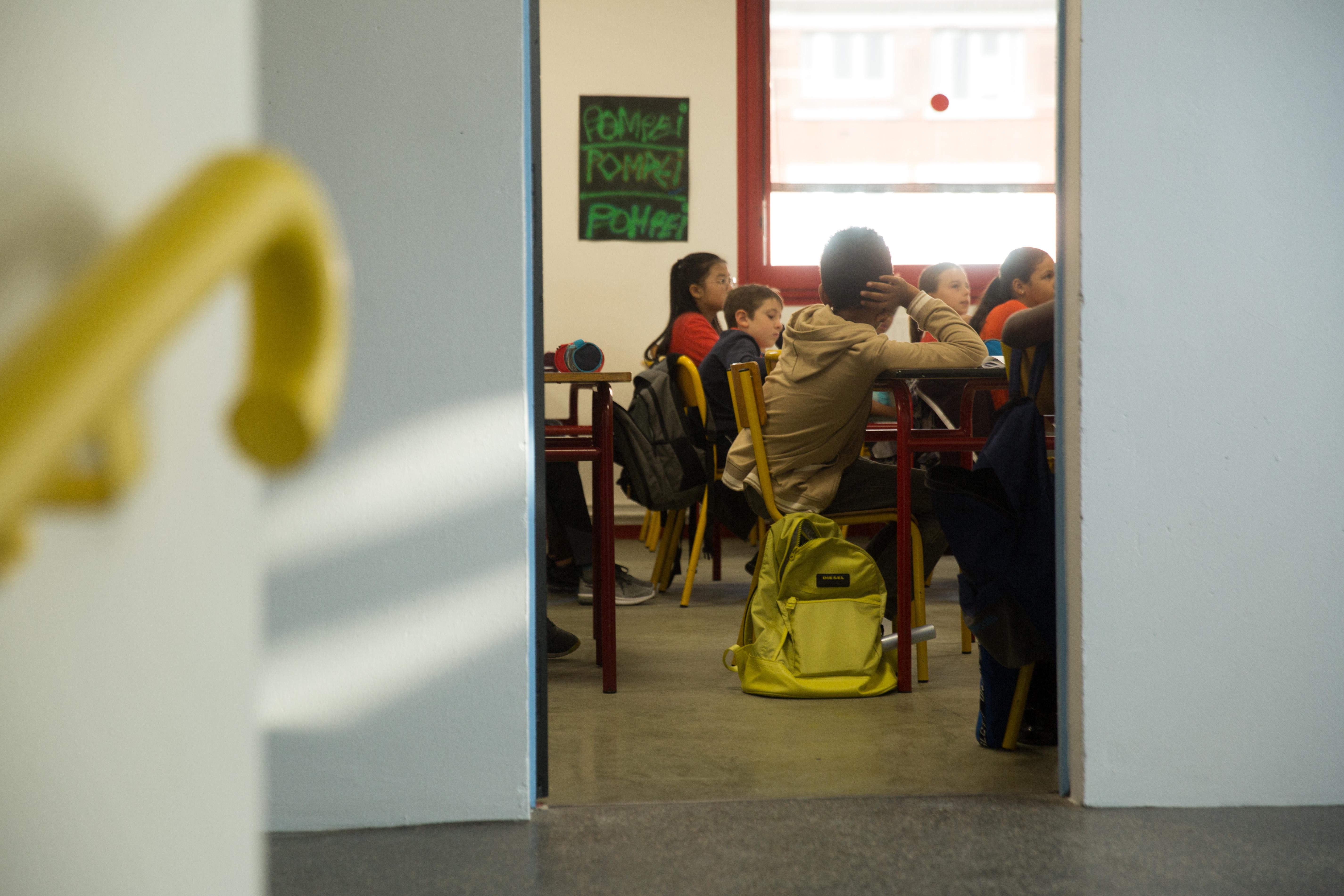 Classe de collège vue depuis le haut d'un escalier via une porte ouverte