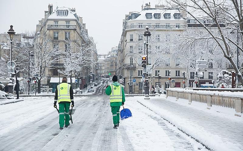 Rues de Paris sous la neige, dans lesquelles deux agent·es de la Propreté marche avec une pelle et une brouette