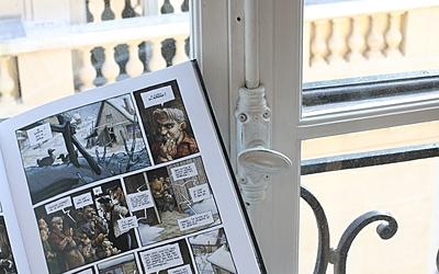 Bande dessinée ouverte devant une fenêtre