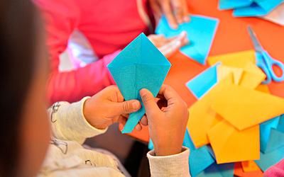 Une enfant fabrique une origami.