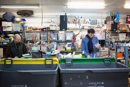 Deux hommes dans un atelier en train de trier et réparer des objets et équipements