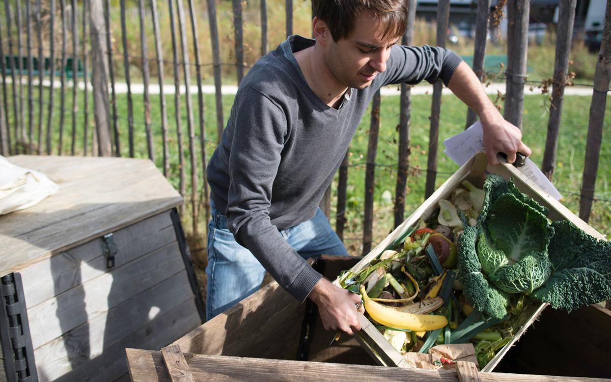 Personne en train d'ajouter ses biodéchets dans un composteur