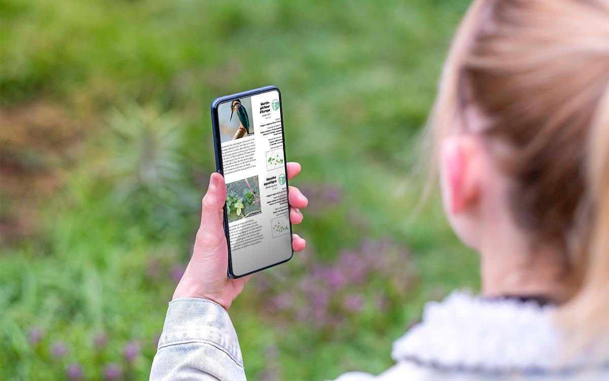 Une jeune fille consulte l'Atlas de la Nature de Paris sur son smartphone