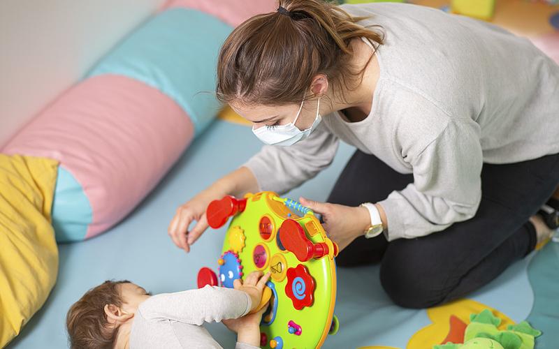 Professionnelle de la petite enfance jouant avec un enfant dans une crèche
