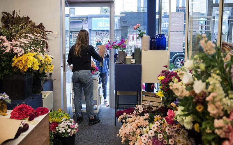 Chez une fleuriste, la commerçante, au pas de sa porte, délivre un bouquet à une cliente qui se trouve à l'extérieur.