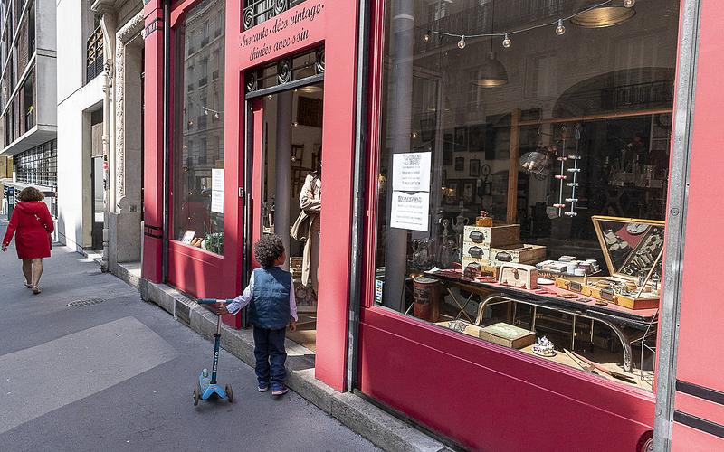Devant une façade de commerce rouge de brocante, un enfant attend ses parents avec sa trottinette