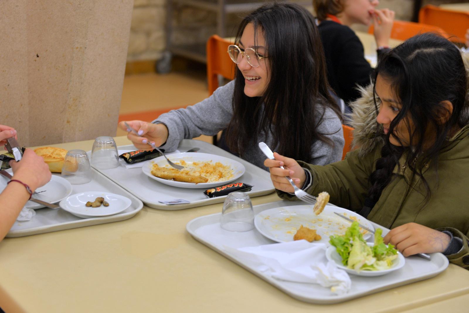 Restauration scolaire cité scolaire Jacques Décour 9e 3 jeunes mangent à table, 2 jeunes filles sont côte à côte, celle de gauche sourit à son ami assit en face. .
