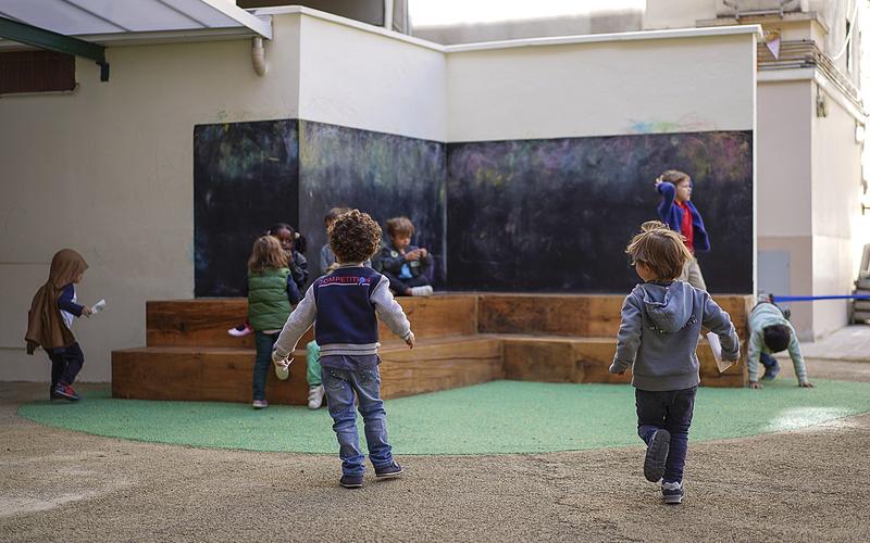 Dans une cour d'école maternelle, des enfants jouent sur des gradins et d'autres courent