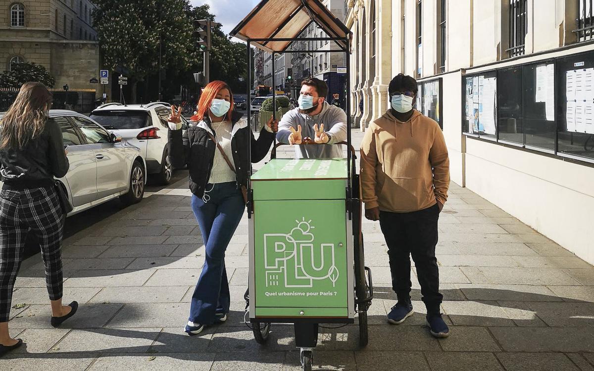 """Triporteur vers avec le logo """"PLU"""", entouré de 3 personnes amenées à animer les temps d'échange avec les habitants et habitantes."""