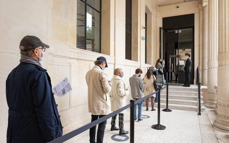 Une file de personnes portant chacun et chacune un masque attend devant un lieu culturel.