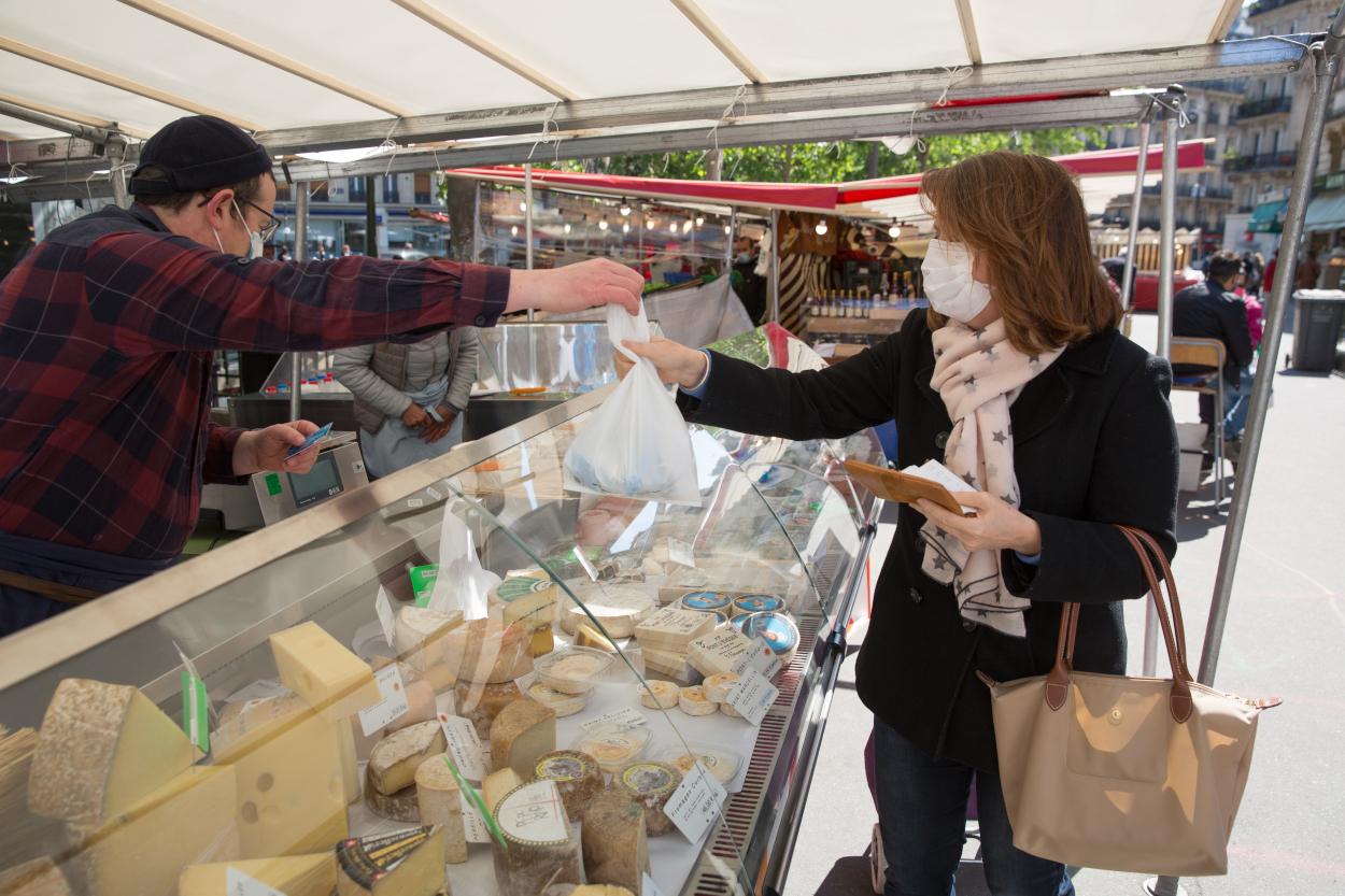 Cliente devant un étal de fromager