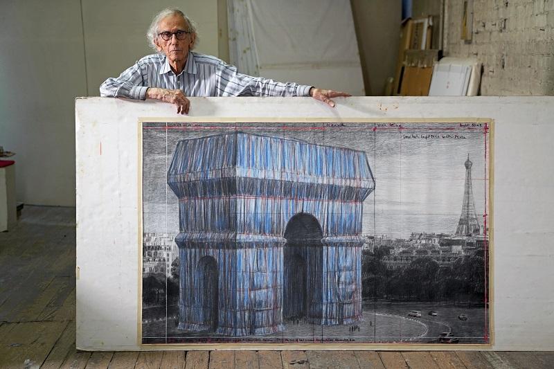 Christo dans son studio avec un dessin préparatoire de L'Arc de Triomphe empaqueté