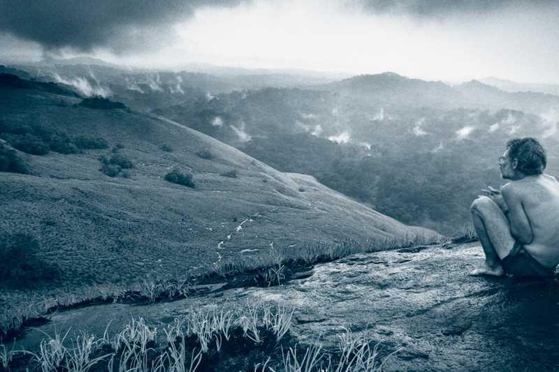 Michael Fay accroupit au pied d'une montagne