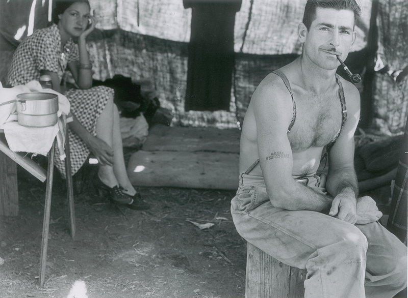 Unemployed lumber worker goes with his wife to the bean harvest. Note social security number tattooed on his arm. Oregon 1939 Dorothea Lange