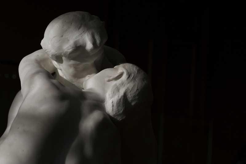 Le Baiser d'Auguste Rodin en marbre, détail, sur fond sombre