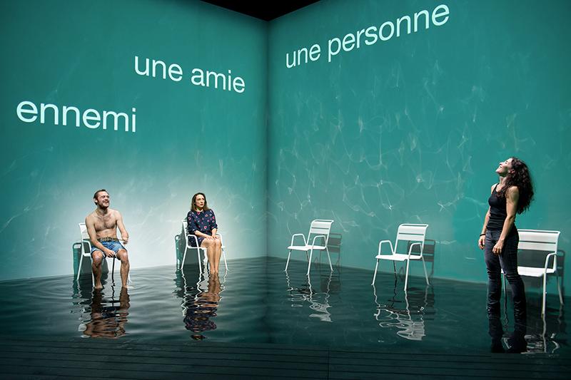Trois personnages sont assis sur des chaises blanches, les pieds dans l'eau : un ennemi, une amie et une personne
