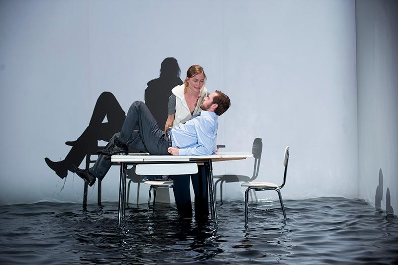 Un homme est allongé sur une table qui flotte dans l'eau, une femme se penche sur lui